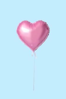 Розовый шар в форме сердца, изолированный на синем