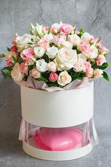 ピンクのハート型のムースケーキと美しい花の大きな花束