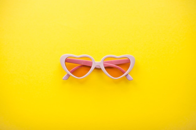 Розовые солнцезащитные очки в форме сердца, изолированные на желтом фоне