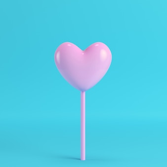Pink heart on a stick on bright blue background