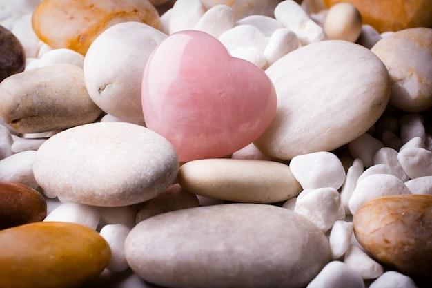 Розовый камень сердца на камне спа.
