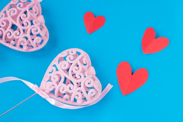 Pink heart with little red hearts on blue background
