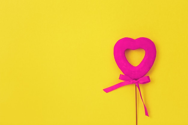 Pink heart on a yellow surface, bow,love
