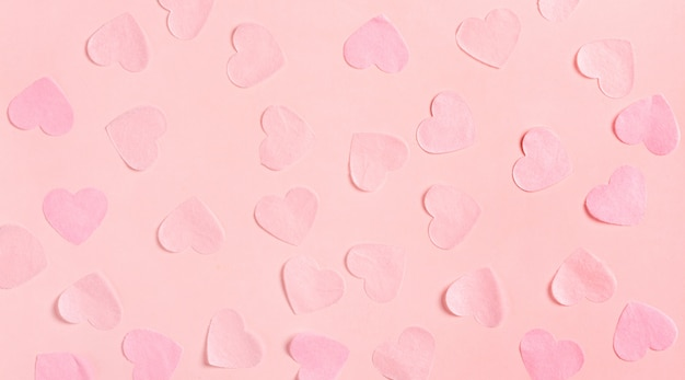Pink hearts made of paper on a pink surface