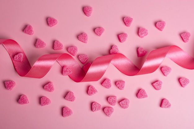 리본 파스텔 핑크 배경에 핑크 하트입니다. 발렌타인 데이에 대한 낭만적 인 배경