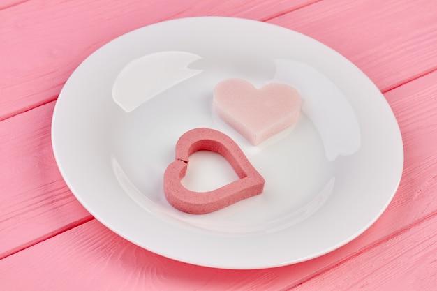 흰색 접시에 핑크 하트입니다. 발렌타인 하트와 핑크 나무 배경에 도자기 접시. 해피 발렌타인 데이 휴가.