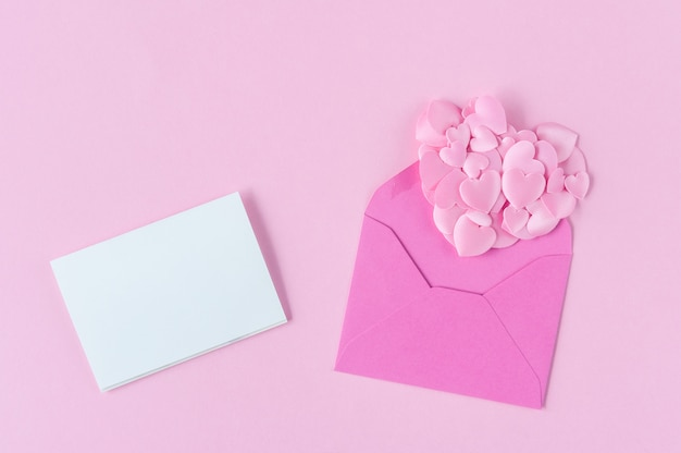 Pink hearts out of open envelope and blank greeting card
