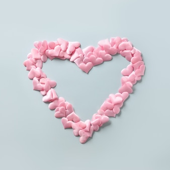 Pink hearts in shape in big heart on blue background, valentine's day greeting card.