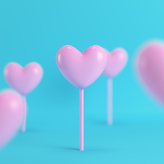 Pink hearts on a stick on bright blue background
