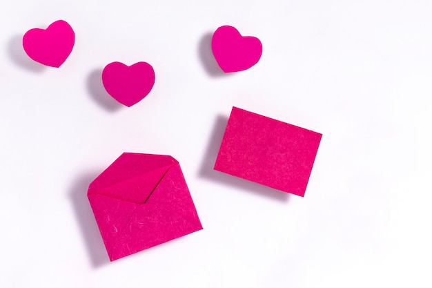 Pink hearts with envelope on white paper surface