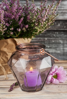 Pink heather and candle in geometrical glass vase