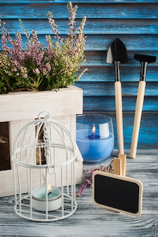 Pink heather, lit blue candle and gardening tools