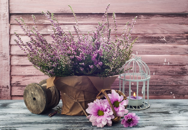 Pink heather in pot, chrysanthemum with candles