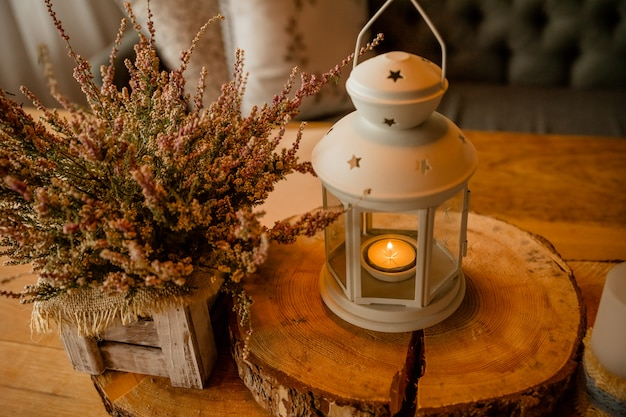 Pink heather in wooden box.autumn decor with candles. white lantern with burning candle.home decoration for cozy atmosphere.
