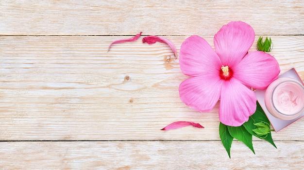 핑크 히비스커스 꽃과 흰색 나무 바탕에 크림의 항아리.
