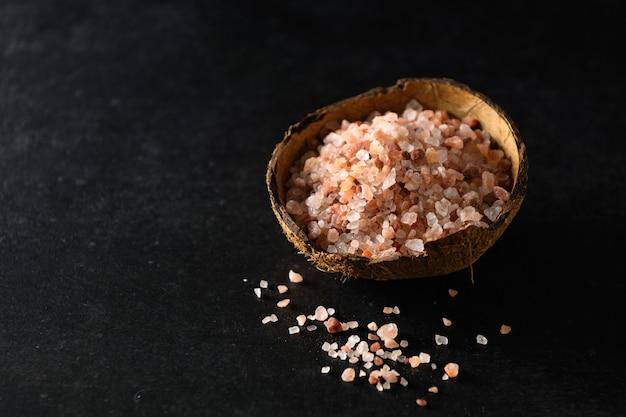 Розовая гималайская крупная соль в кокосовой миске на темно-серой поверхности