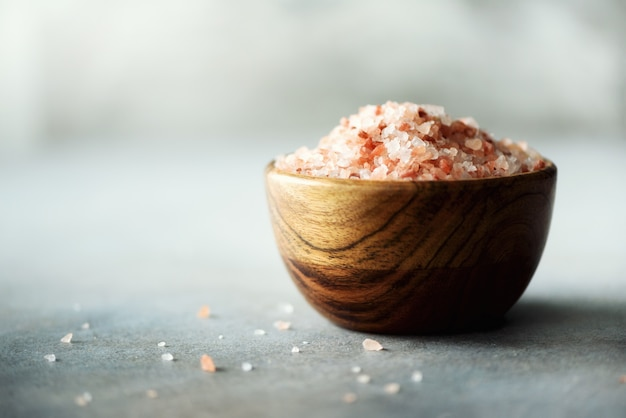 Pink himalayan salt crystals and powder in wooden bowls on grey concrete. healthy diet without salt.
