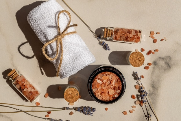Pink himalayan salt in the glass bottles with rolled towel on marble background. close up of pink crystals of sea salt. spa body care concept.