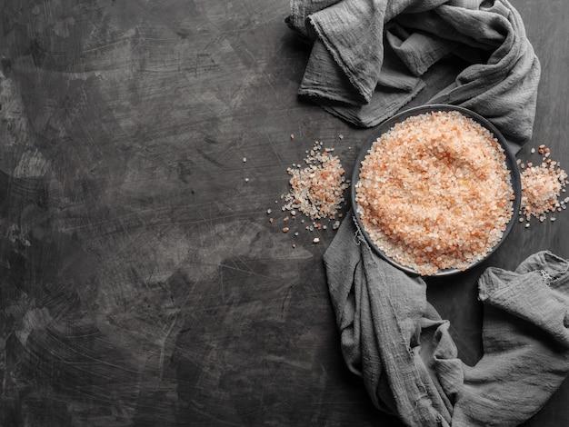 灰色の布でテーブルの上のプレートにピンクのヒマラヤの塩。上面図。