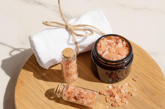 木の板に巻いたタオルとガラス瓶のピンクのヒマラヤの塩。海塩のピンクの結晶のクローズアップ。スパボディケアのコンセプト