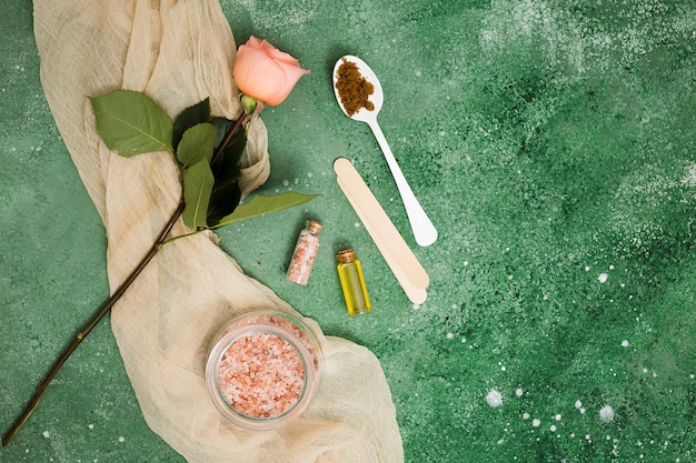 Pink himalayan salt in jar; rose; essential oil and coffee ground in spoon against green textured backdrop