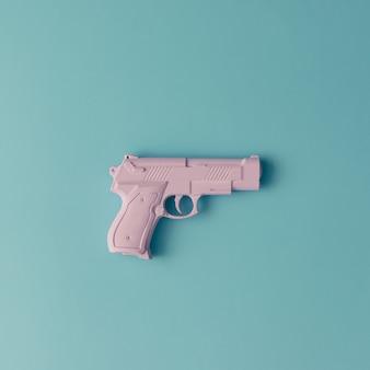 Розовый хипстерский пистолет на голубой пастельной поверхности