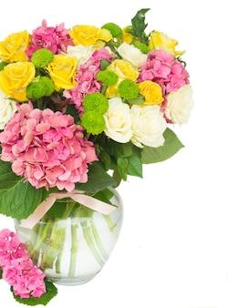 花瓶に白と黄色のバラとピンクのオルテンシアの花が孤立してクローズアップ