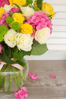 花瓶に白と黄色のバラとピンクのオルテンシアの花のクローズアップ