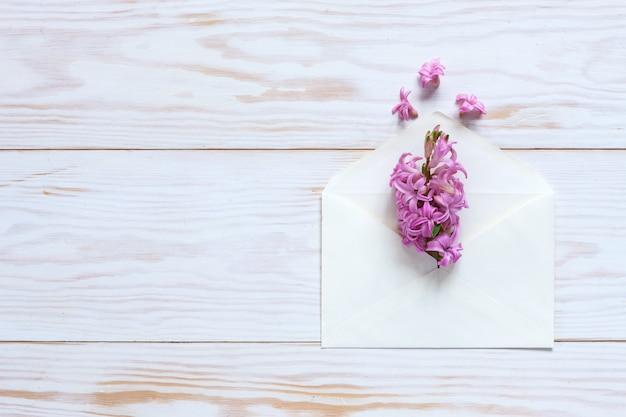 Pink hyacinth in white paper envelope