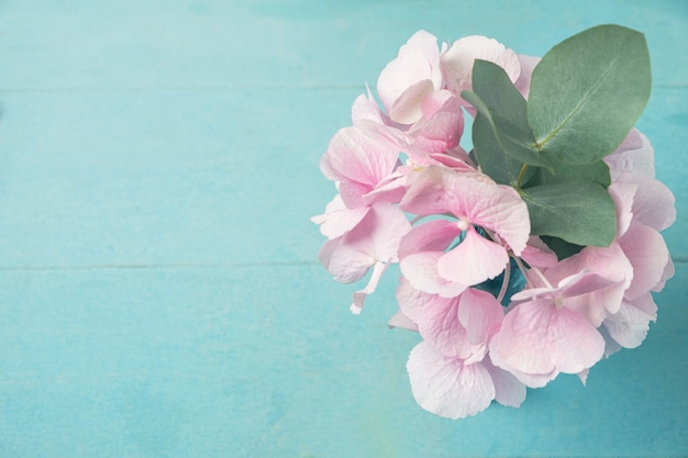 Pink hydrangea flower with a branch of eucalyptus leaves in a vase on a blue wooden table
