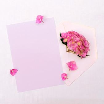白い背景の上の封筒にピンクのアジサイ。デザインの場所とグリーティングカード。