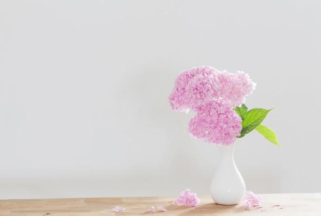背景の白い壁の木製の棚に白い花瓶のピンクのアジサイ