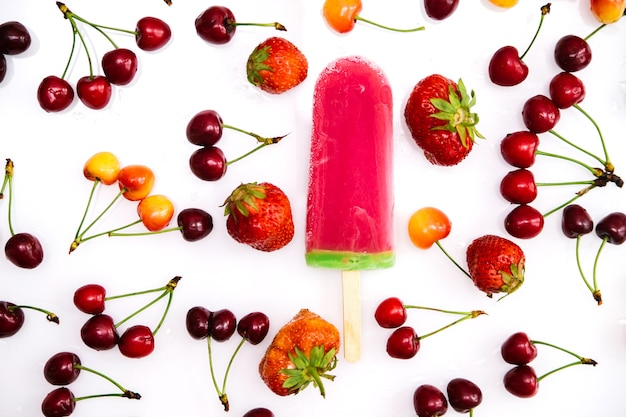 Pink ice cream among cherries and strawberries on a white background.summer refreshing dessert.
