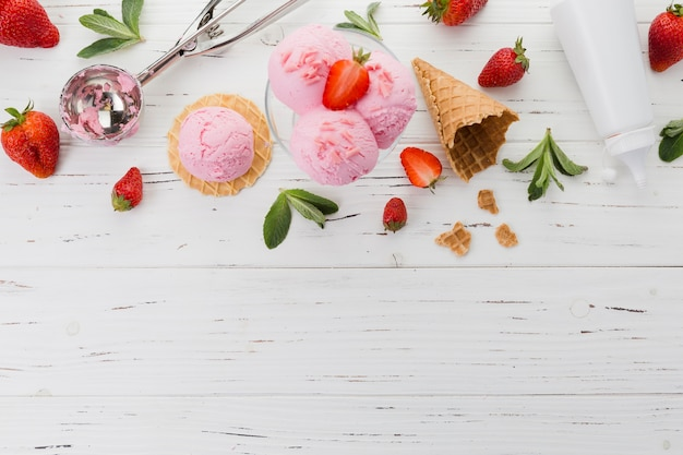 Pink ice cream with strawberries and scooper