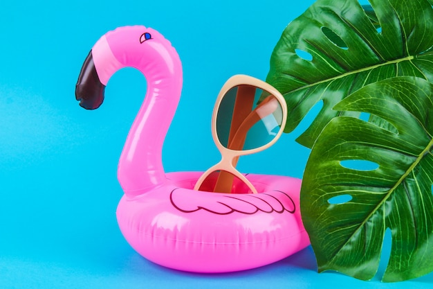Pink inflatable flamingo on blue background with sunglasses and monstera leaves.