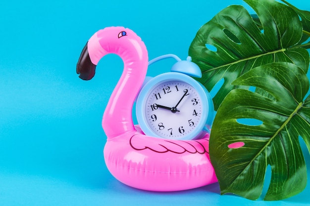 Pink inflatable flamingo on blue with monstera leaves and clock.