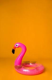 Розовый надувной круг фламинго на желтой поверхности с пространством для текста