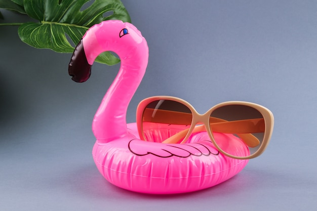 Pink inflatable flamingo on gray background with sunglasses and monstera leaves.