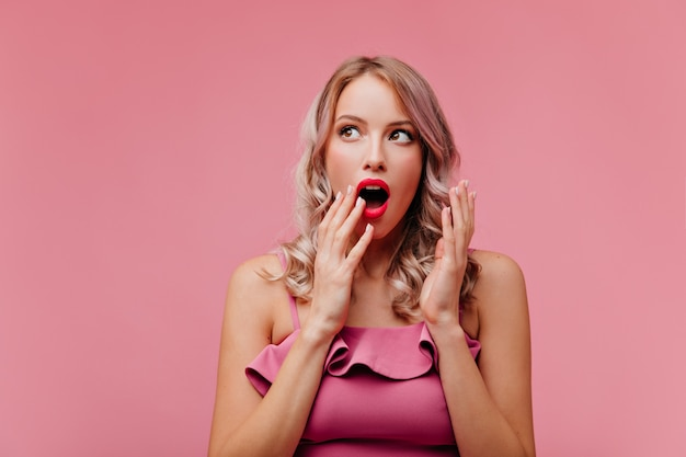 On pink isolated wall young woman with bright make-up in pink design dress, with painted pink lips demonstrates hug posing in front of camera