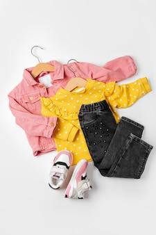 ピンクのジャケットとハンガーのジャンパーとスニーカーのジーンズ。白い背景の上の春または秋のベビー服とアクセサリーのセットです。ファッションキッズ衣装。フラットレイ、上面図