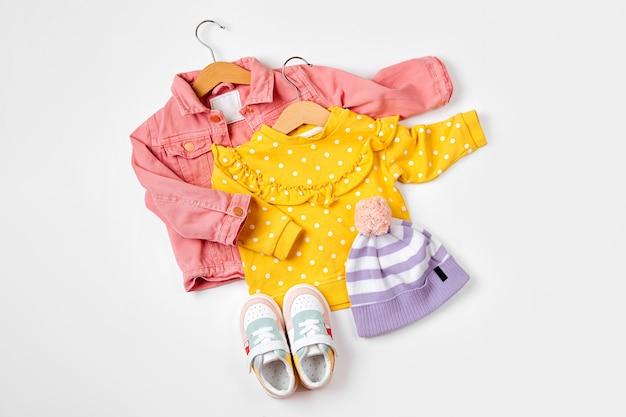스니커즈가 달린 옷걸이에 분홍색 재킷과 점퍼. 흰색 바탕에 봄이나 가을을 위한 아기 옷과 액세서리 세트. 패션 키즈 복장. 평평한 평지, 평면도
