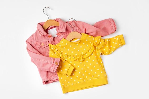 ピンクのジャケットとハンガーの黄色のジャンパー。白い背景の上の春または秋のベビー服とアクセサリーのセットです。ファッションキッズ衣装。フラットレイ、上面図