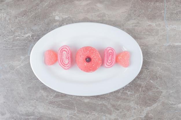 ピンクのゼリー菓子とクッキーが大理石の表面の大皿に並べられています