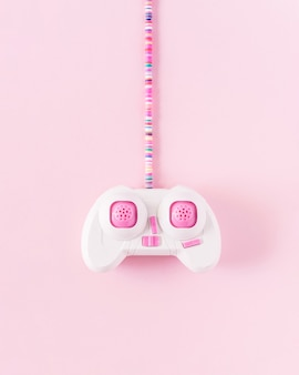 Розовый джойстик с красочным кабелем на мягком пастельно-розовом фоне. минималистичная плоская планировка.