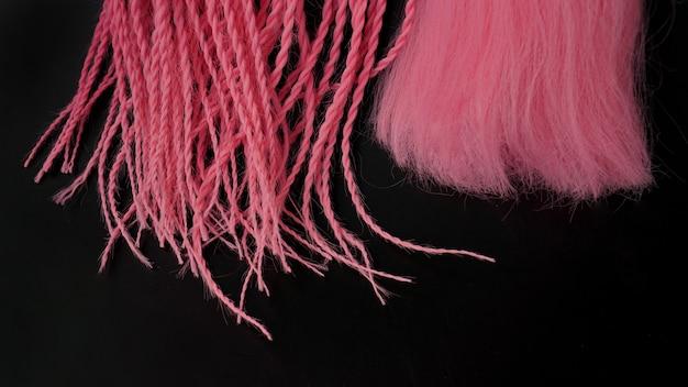 Розовый канекалон висит и заплетается на черном фоне - кончики крупным планом