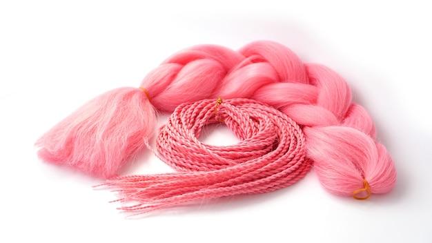 Розовый канекалон висит и заплетается на белом фоне. фото для каталога или парикмахера