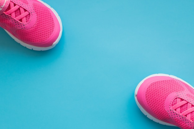 Pink kids training shoes isolated on blue background.child clothing, foot wear and fashion.children's sports sneakers .pair of girl sports shoes. copy space