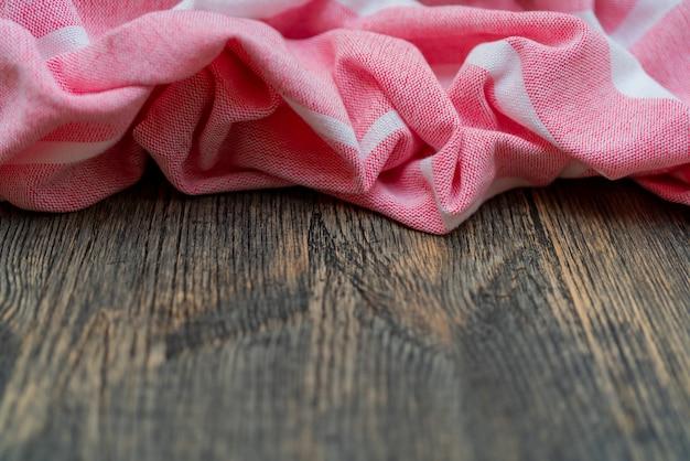 Розовое кухонное полотенце лежит на деревянном столе. текстура крашеного дерева. фактурные складки ткани.