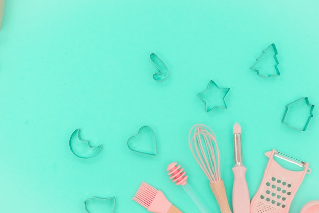 Pink kitchen utensils. greater, whisk and iron cooking form. top view