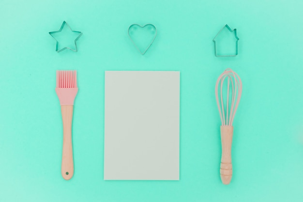 Pink kitchen utensils with blank note. greater, whisk and iron cooking form. top view